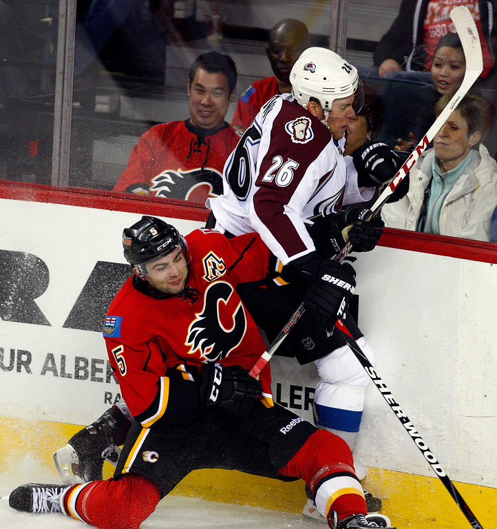 . Colorado Avalanche\'s Paul Stastny, right, and Calgary Flames\' Mark Giordano crash into the boards during the second period of an NHL hockey game Thursday, Jan. 31, 2013, in Calgary, Alberta. (AP Photo/The Canadian Press, Jeff McIntosh)