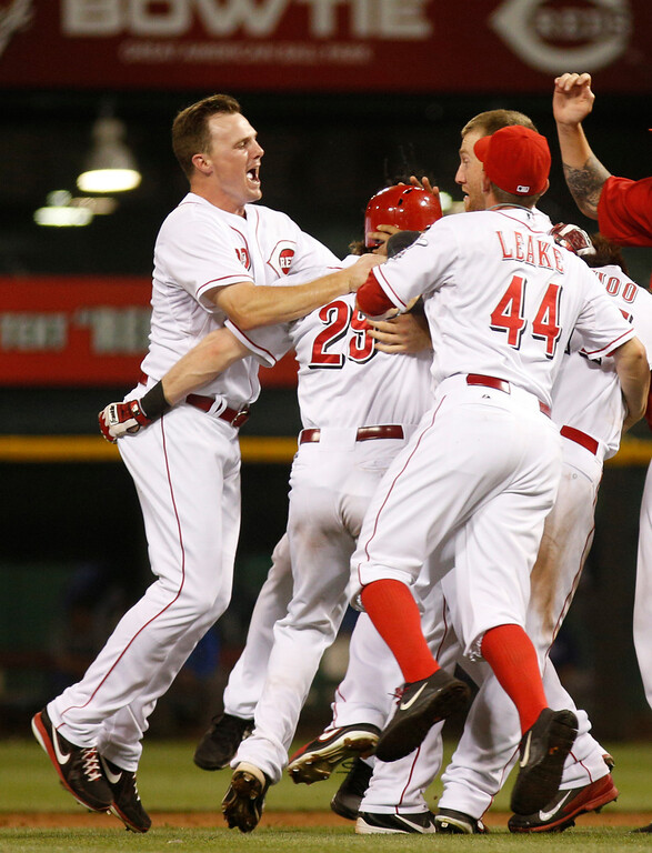 . Cincinnati Reds\' Jay Bruce, left, and Mike Leake, right, celebrate with Ryan Hanigan, middle, after Hanigan hit an RBI game-winning double off Los Angeles Dodgers relief pitcher Ronald Belisario in the ninth inning during a baseball game, Sunday, Sept. 8, 2013, in Cincinnati. The Reds won 3-2. (AP Photo/David Kohl)
