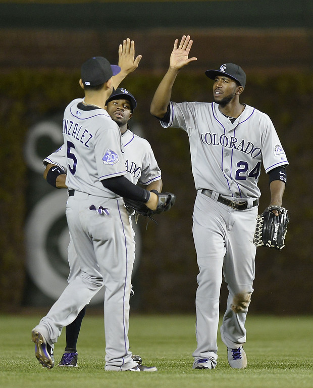 . Outfielders Carlos Gonzalez #5, Eric Young Jr. #1 and Dexter Fowler #24 of the Colorado Rockies celebrate a win over the Chicago Cubs on May 14, 2013 at Wrigley Field in Chicago, Illinois. The Rockies defeated the Cubs 9-4.    (Photo by Brian Kersey/Getty Images)