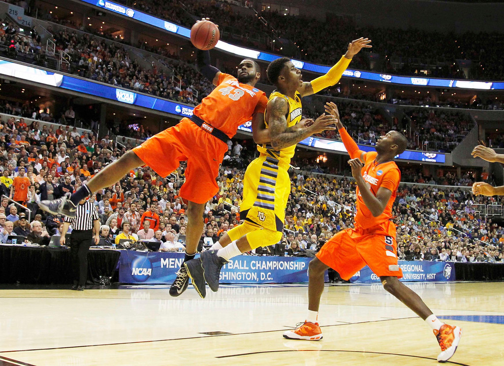 . Syracuse Orange forward James Southerland (L) rebounds against Marquette Golden Eagles guard Vander Blue as Syracuse Orange center Baye Keita (R) follows the action during the second half in their East Regional NCAA men\'s basketball game in Washington, March 30, 2013. REUTERS/Jason Reed