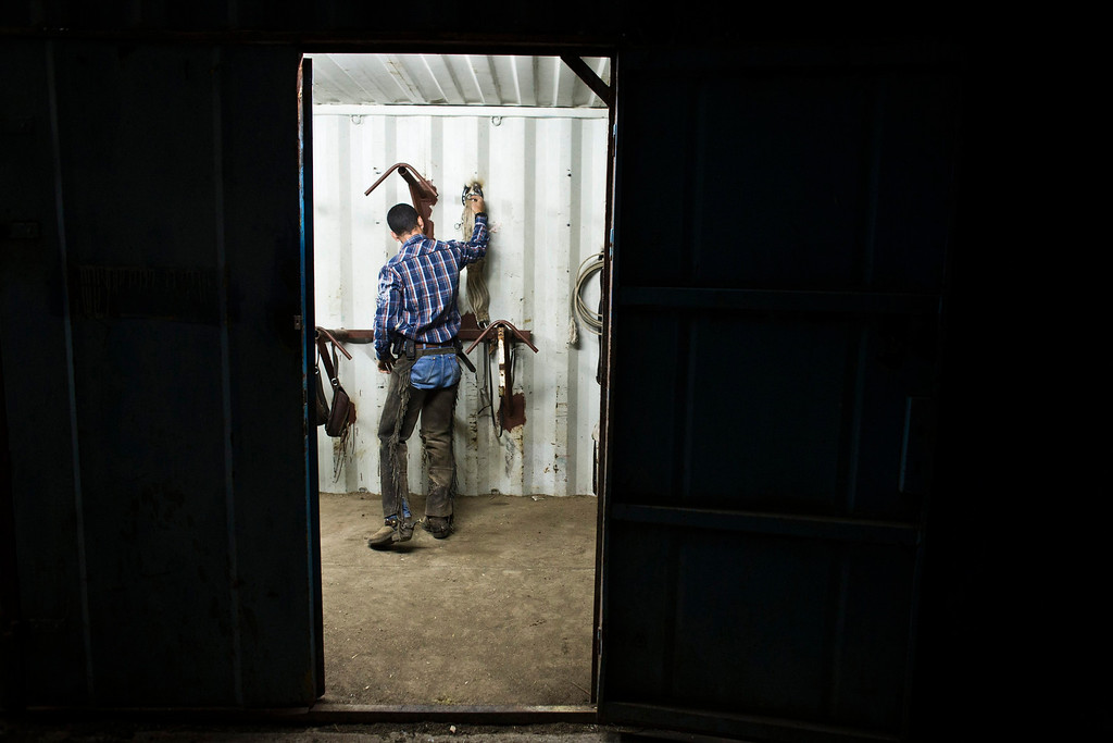 . Amit, an Israeli cowboy, gets ready in the early morning a the ranch just outside Moshav Yonatan, a collective farming community, about 2 km (1 mile) south of the ceasefire line between Israel and Syria in the Golan Heights May 21, 2013. REUTERS/Nir Elias
