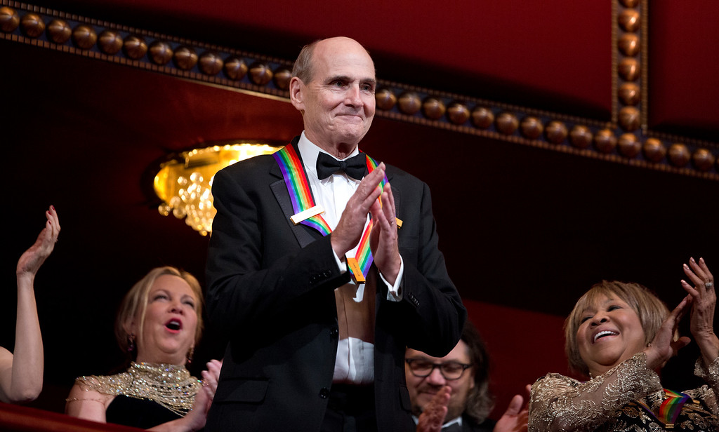 . Recipient of the 2016 Kennedy Center Honor award, musician James Taylor, acknowledges the applause during the Kennedy Center Honors gala at the Kennedy Center in Washington, Sunday, Dec. 4, 2016. On the right is honoree gospel and blues singer Mavis Staples. (AP Photo/Manuel Balce Ceneta)