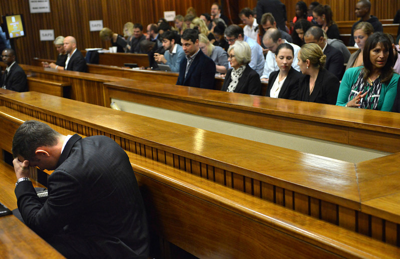 . Oscar Pistorius, left, in the dock on the second day of his trial at the high court in Pretoria, South Africa, Tuesday, March 4, 2014. Pistorius is charged with murder for the shooting death of his girlfriend, Reeva Steenkamp, on Valentines Day in 2013. (AP Photo/Antoine De Ras, Pool)