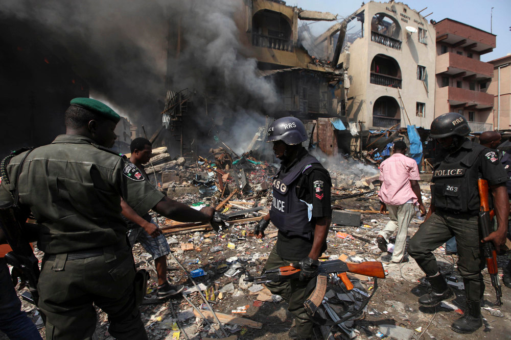 Description of . Nigeria policemen at the scene of a warehouse and residential home fire on Lagos Island in Lagos, Nigeria, Wednesday, Dec. 26, 2012. An explosion ripped through a warehouse Wednesday where witnesses say fireworks were stored in Nigeria\'s largest city, sparking a fire. It wasn\'t immediately clear if anyone was injured in the blast that firefighters and locals struggled to contain. (AP Photos/Sunday Alamba)