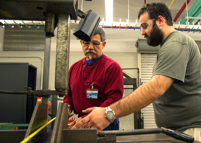 Instructor Jack Esparza(left) helps student Zac Ramirez cuting a bar in Engineering Lab.
