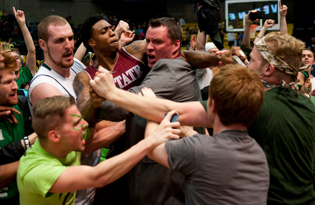 . In this Thursday, Feb. 27, 2014 photo, New Mexico State\'s Daniel Mullings, center left in red and white jersey, is involved in a brawl involving players and fans who came onto the court when New Mexico State guard K.C. Ross-Miller hurled the ball at Utah Valley\'s Holton Hunsaker seconds after the Wolverines\' 66-61 overtime victory against the Aggies on Thursday night. Feb. 27, 2014.  (AP Photo/The Daily Herald, Grant Hindsley)