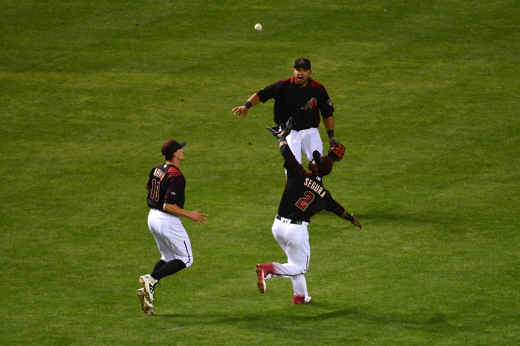 . Jean Segura #2 of the Arizona Diamondbacks catches the fly ball as teammates Nick Ahmed #13 and Yasmany Tomas #24 watch in the fourth inning of the game against the Colorado Rockies at Chase Field on April 30, 2016 in Phoenix, Arizona.  (Photo by Jennifer Stewart/Getty Images)