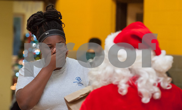 12/12/17 Wesley Bunnell | Staff New Britain OIC held their annual Christmas Party on Tuesday afternoon featuring food, music and presents for all members. Nas-zaira Watkins smiles as she walks up to receive a present from Santa.