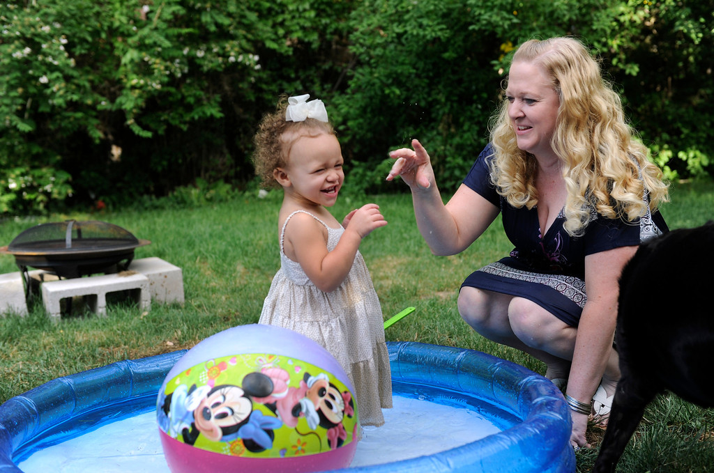 . DENVER, CO - JUNE 25: Laura and Keenon Stillman are joined by their children for a summer meal outside in the family backyard. Laura and granddaughter Aspen, 1, share some playtime in the backyard kiddie pool. (Photo By Kathryn Scott Osler/The Denver Post)