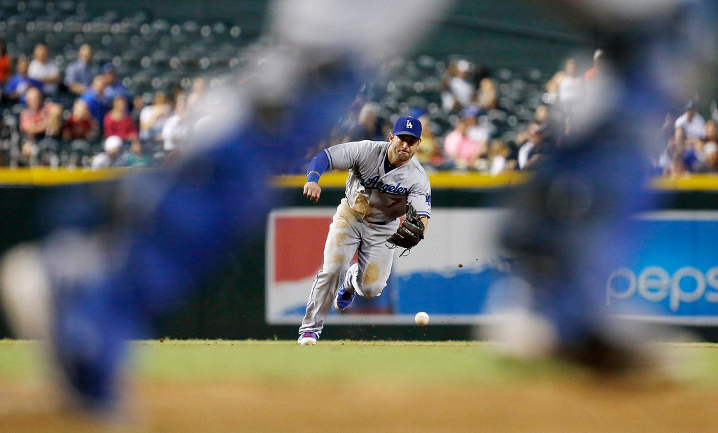 . Framed by Los Angeles Dodgers catcher A.J. Ellis, Dodgers\' Nick Punto fields a ground ball hit by Arizona Diamondbacks\' Chris Owings in the fifth inning of a baseball game on Monday, Sept. 16, 2013, in Phoenix.  The Diamondbacks defeated the Dodgers 2-1.  AP Photo/Ross D. Franklin)