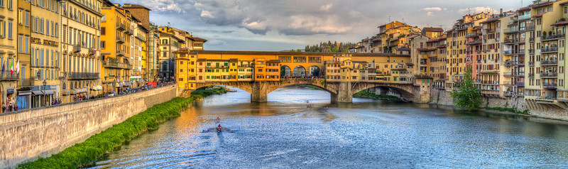 Panoramic view of canoes on the Arno River going under the Ponte Verde Bridge in Florence, Italy