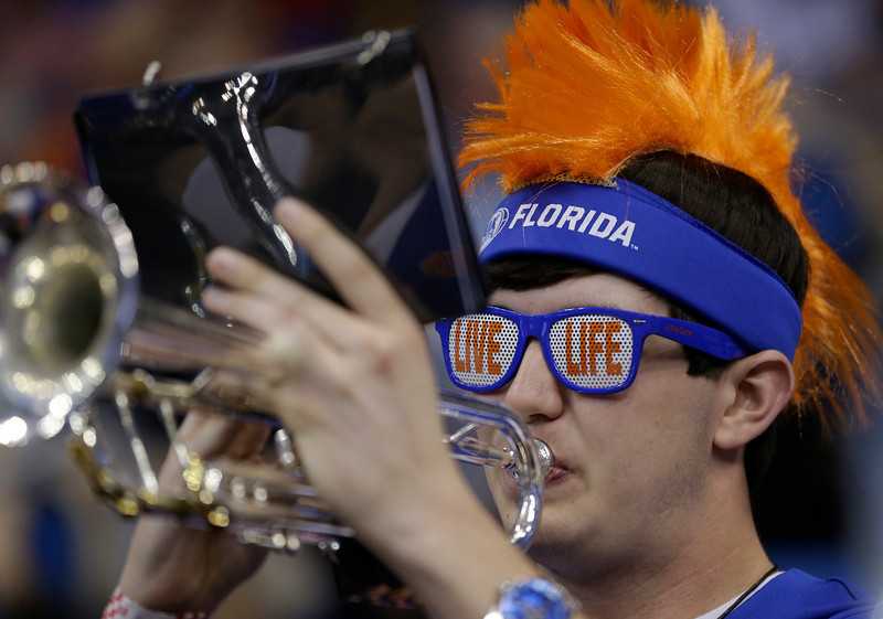 . Florida band member, Evan Glass performs before a third-round game in the NCAA college basketball tournament against Pittsburgh, Saturday, March 22, 2014, in Orlando, Fla. (AP Photo/John Raoux)