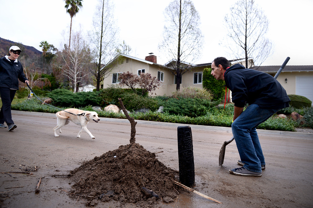 . Chad Exley, of Azusa, takes a break from cleaning up mud at his mother Trish Emery\'s home on Rainbow Drive in Glendora to greet a neighbor and her dog Saturday, March 1, 2014. The neighborhood sits below the Colby Fire burn area. (Photo by Sarah Reingewirtz/Pasadena Star-News)
