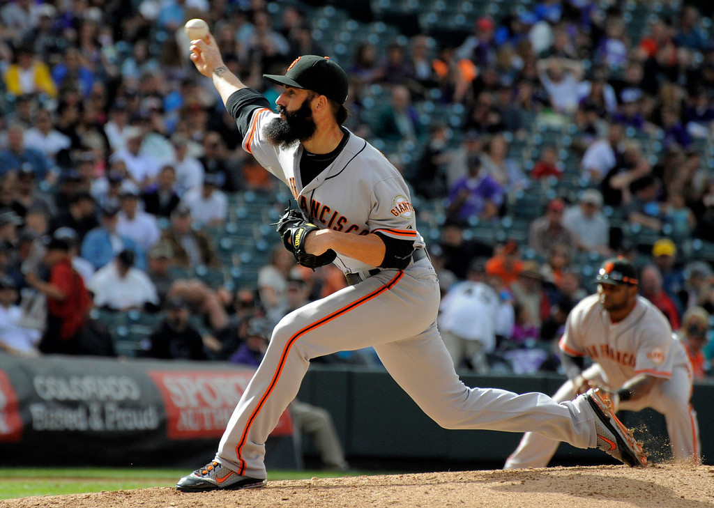. San Francisco Giants relief pitcher Brian Wilson, left, throws to the plate against the Colorado Rockies during the ninth inning of a baseball game Thursday, April 12, 2012, in Denver. The Giants defeated the Rockies 4-2. (AP Photo/Jack Dempsey)