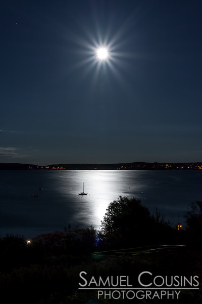 The Hunter's Moon rising over Casco Bay. A small sailboat is moored in the reflected moonlight.