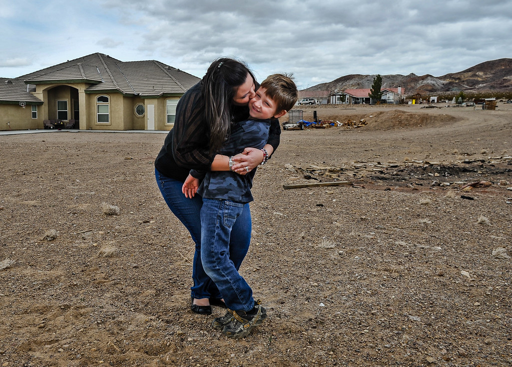 . Reanna Banks, 33, hugs her son Aiden, 6, in the front yard of their family\'s 10-acre land parcel in Hinkley, Calif. on Thursday, March 7, 2013. Banks has been a dovoted resident for most of her adult life, and her son is a third generation Hinkley resident. (Rachel Luna / San Bernardino Sun)