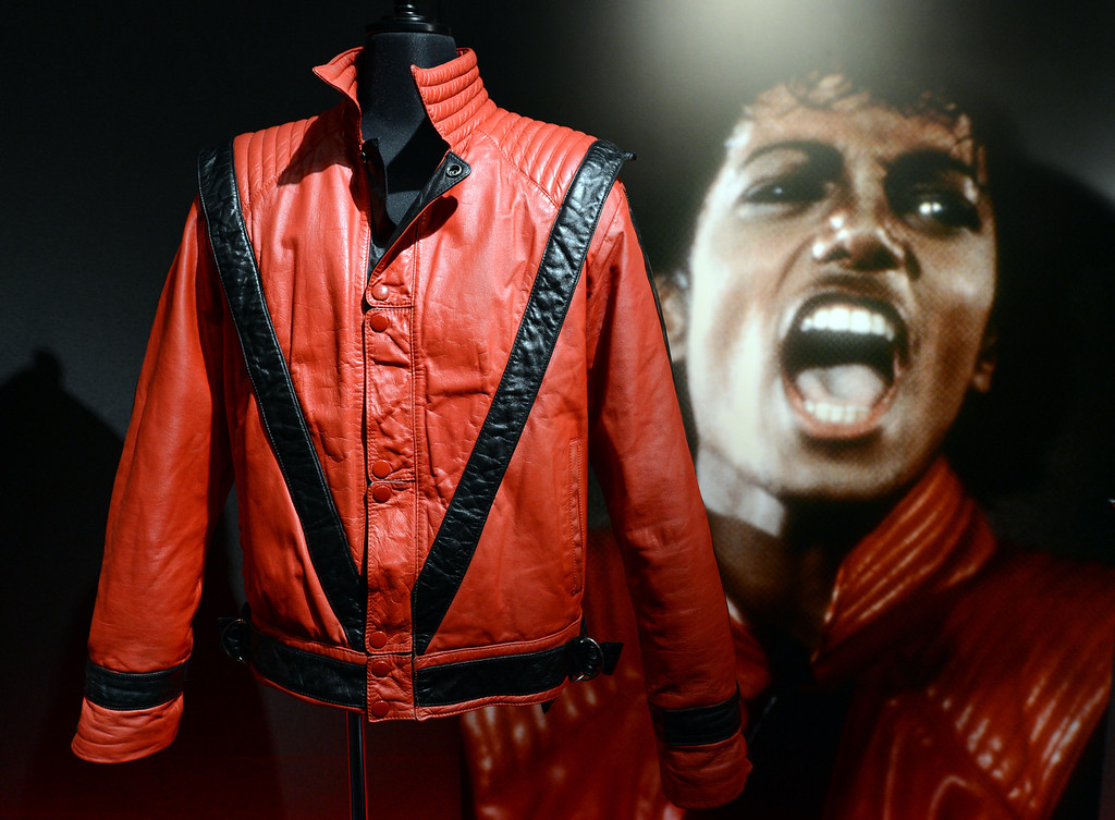 """. Late US pop star Michael Jackson\'s \""""Thriller\"""" style jacket (L) is displayed next to a picture of him during the press preview of \""""The Collection of Tompkins and Bush: Michael Jackson\"""" in Tokyo on October 17, 2012.             (TOSHIFUMI KITAMURA/AFP/Getty Images)"""