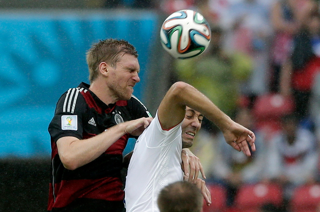 . Germany\'s Per Mertesacker, left, and United States\' Clint Dempsey go for a header during the group G World Cup soccer match between the USA and Germany at the Arena Pernambuco in Recife, Brazil, Thursday, June 26, 2014. (AP Photo/Matthias Schrader)