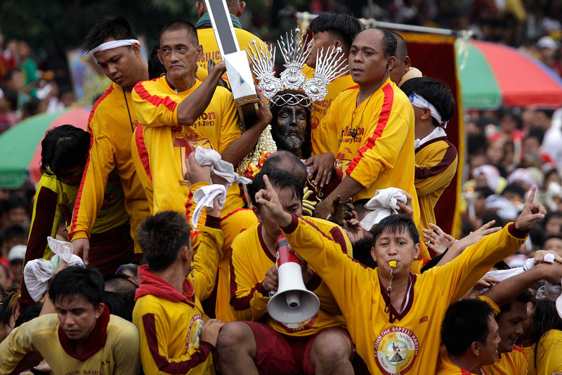 . Filipino devotees surround a centuries-old image of the Black Nazarene during a raucous procession on its feast day Wednesday, Jan. 9, 2013 in Manila, Philippines. Hundreds of thousands of mostly barefoot Roman Catholic devotees joined the annual ritual to demonstrate faith and seek miracle cures for illnesses and a good life. (AP Photo/Aaron Favila)