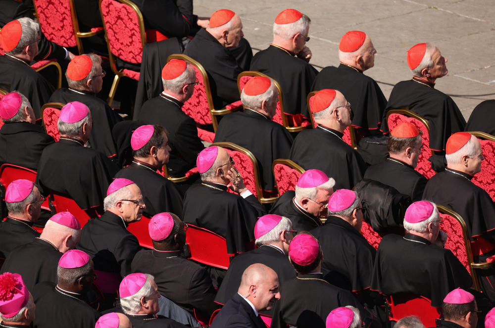 Description of . Archbishops (purple hats) and cardinals (red hats) sit in St Peter\'s Square as Pope Benedict XVI delivers his final weekly public audience on February 27, 2013 in Vatican City, Vatican.  The Pontiff has attended his last weekly public audience before stepping down tomorrow. Pope Benedict XVI has been the leader of the Catholic Church for eight years and is the first Pope to retire since 1415. He cites ailing health as his reason for retirement and will spend the rest of his life in solitude away from public engagements.  (Photo by Oli Scarff/Getty Images)