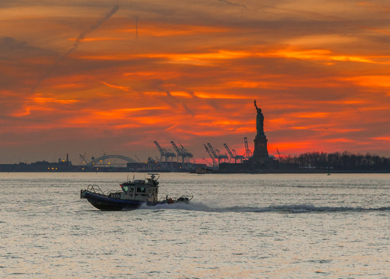 Sun setting behind the Statue of Liberty in New York; NYPD boat cruising past.