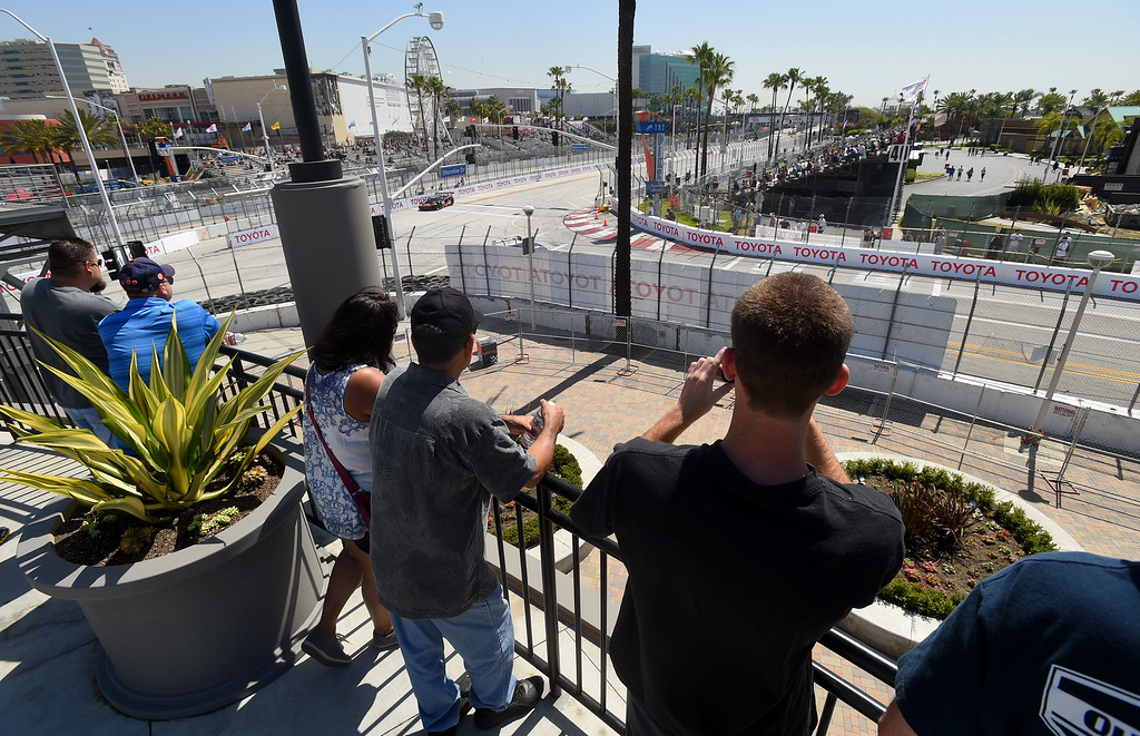 . Race fans watch cars practice from a viewing area atop Restoration Hardware at turn one in Long Beach, CA on Friday, April 17, 2015. The 40th annual Toyota Grand Prix of Long Beach kicked off with practices for all of the racing divisions. (Photo by Scott Varley, Daily Breeze)