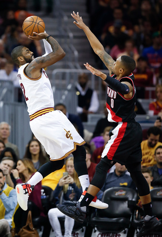 . Cleveland Cavaliers\' Kyrie Irving (2) shoots over Portland Trail Blazers\' Damian Lillard (0) during the second half of an NBA basketball game, Wednesday, Nov. 23, 2016, in Cleveland. The Cavaliers won 137-125. (AP Photo/Ron Schwane)