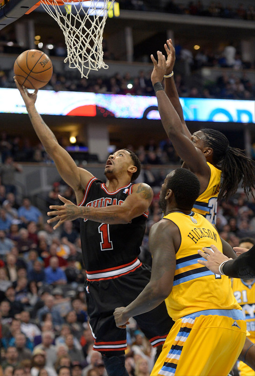 . Chicago Bulls point guard Derrick Rose (1) goes up for a shot past Denver Nuggets power forward Kenneth Faried (35) during the third quarter November 21, 2013 at Pepsi Center. (Photo by John Leyba/The Denver Post)