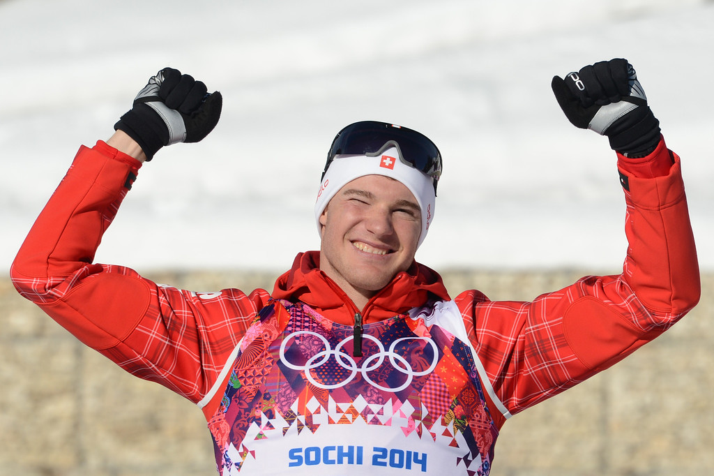 . Gold medalist Switzerland\'s Dario Cologna celebrates on the podium at the Men\'s Cross-Country Skiing 15km Classic Flower Ceremony at the Laura Cross-Country Ski and Biathlon Center during the Sochi Winter Olympics on February 14, 2014 in Rosa Khutor near Sochi. AFP PHOTO / KIRILL KUDRYAVTSEV/AFP/Getty Images