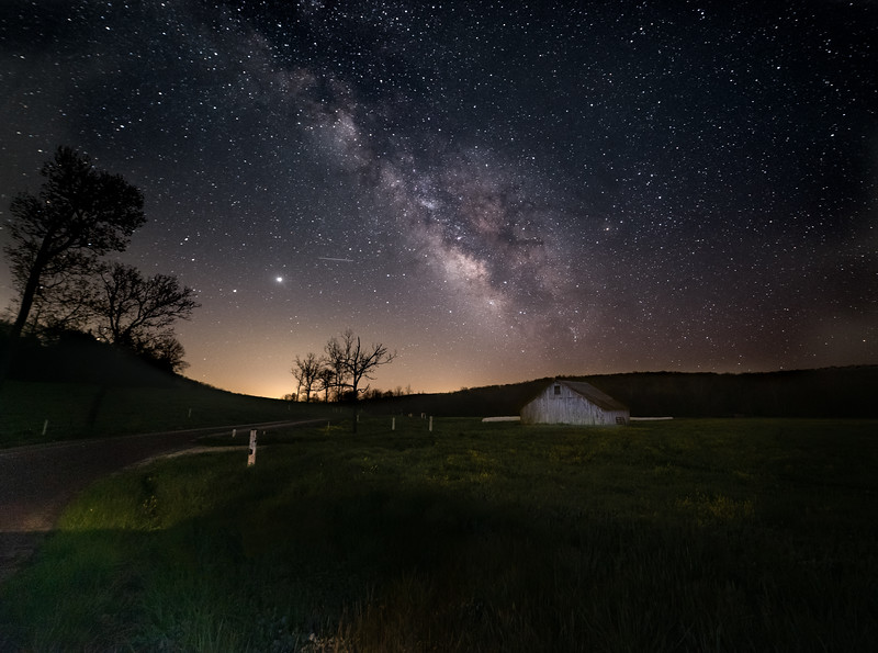 A barn in the distance under the Milky Way