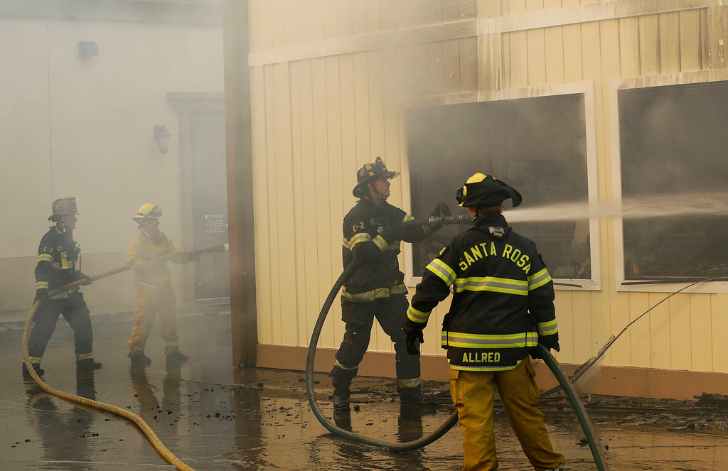 . Firefighters hose down a business complex that included a gun shop in Santa Rosa, Calif., Monday, Oct. 9, 2017. (AP Photo/Jeff Chiu)