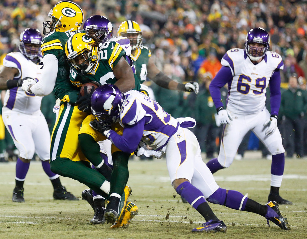 . Green Bay Packers running back DuJuan Harris (26) tries to break a tackle by Minnesota Vikings strong safety Jamarca Sanford (33) during a touchdown run in the first half of an NFL wild card playoff football game Saturday, Jan. 5, 2013, in Green Bay, Wis. (AP Photo/Jeffrey Phelps)