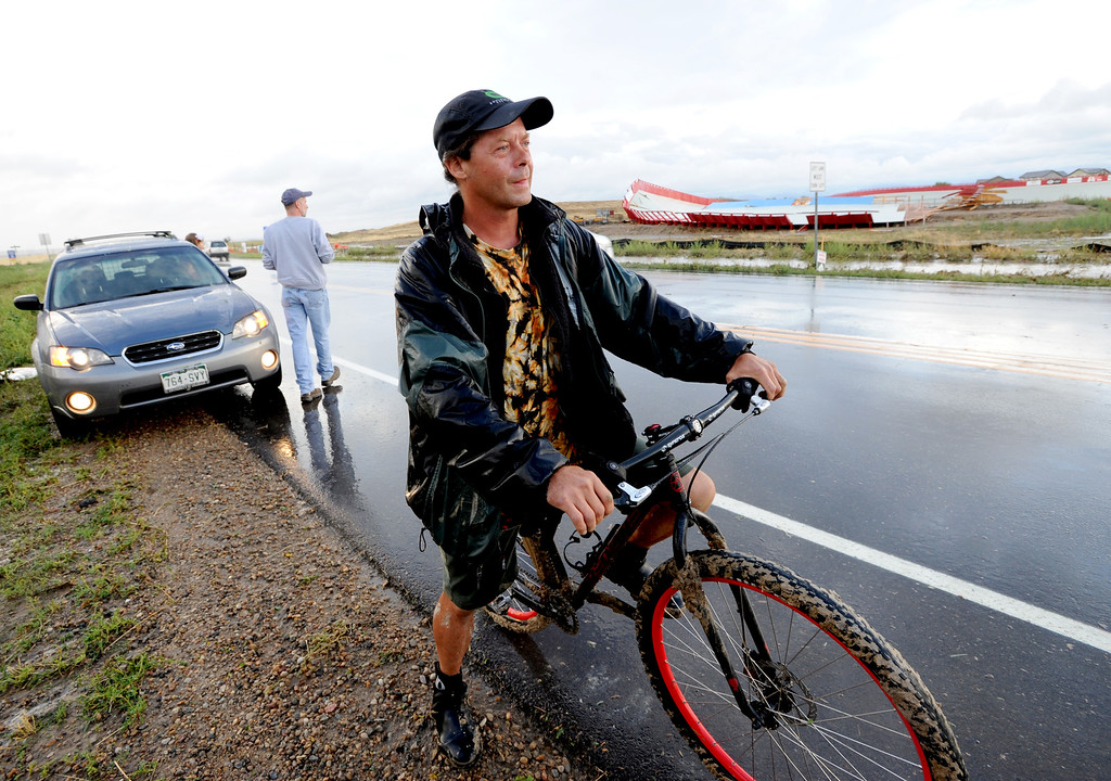 . Mikel Reid, construction foreman for the Erie Velodrome, rides home after looking over the storm damage to the velodrome, in background,  in Erie, Colorado on August 3, 2013.He said he will go back to work on it tomorrow. For more photos and videos of the storm damage, go to www.dailycamera.com. Cliff Grassmick  / August 3, 2013