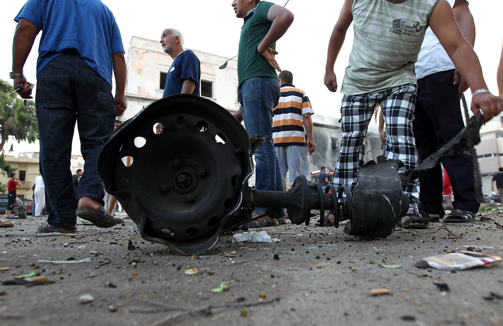 . Libyans gather near the remains of a burnt car on the site of a powerful blast near a foreign ministry building on September 11, 2013 in the eastern Libyan city of Benghazi. The explosion comes on the first anniversary of an attack by militants on the United States consulate in Benghazi, which killed four Americans, including the ambassador. ABDULLAH DOMA/AFP/Getty Images