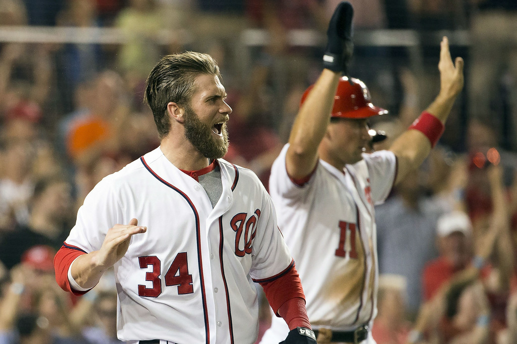 . Washington Nationals Bryce Harper, left, and Ryan Zimmerman cheer on teammate Ian Desmond after scoring on his three-run double during the sixth inning of a baseball game against the Colorado Rockies at Nationals Park, on Monday, June 30, 2014, in Washington. (AP Photo/Evan Vucci)