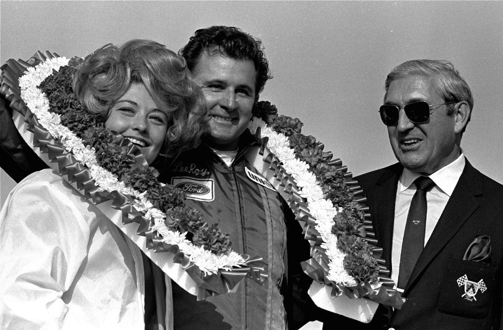 Description of . Lee Roy Yarbrough and his wife, draped in winners flowers, are all smiles in victory lane after Lee Roy won the Daytona 500 stock car race February 23, 1969 at the Daytona International Speedway driving a 1969 Ford.  (AP Photo/TY)