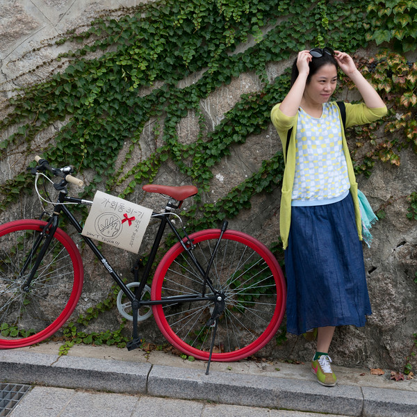 Woman standing near bicycle, Bukchon Hanok Village, Seoul, South Korea