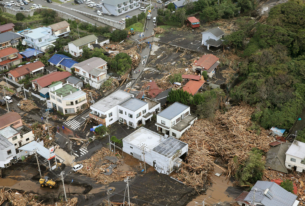 . Several houses in a residential area in Oshima are covered by debris of mudslides after a powerful typhoon hit Izu Oshima island, about 120 kilometers (75 miles) south of Tokyo Wednesday morning, Oct. 16, 2013.  (AP Photo/Kyodo News)