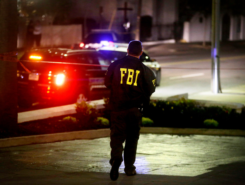 . An FBI agent walks across the street from the Emanuel AME Church following a shooting Wednesday, June 17, 2015, in Charleston, S.C. (AP Photo/David Goldman)