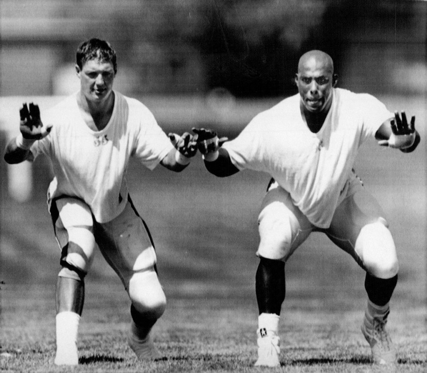 . July 19, 1991: Broncos linebackers Rick Dennison, left, and rookie Kenny Walker linked fingers while copying each others steps during an impromptu drill. (The Denver Post)