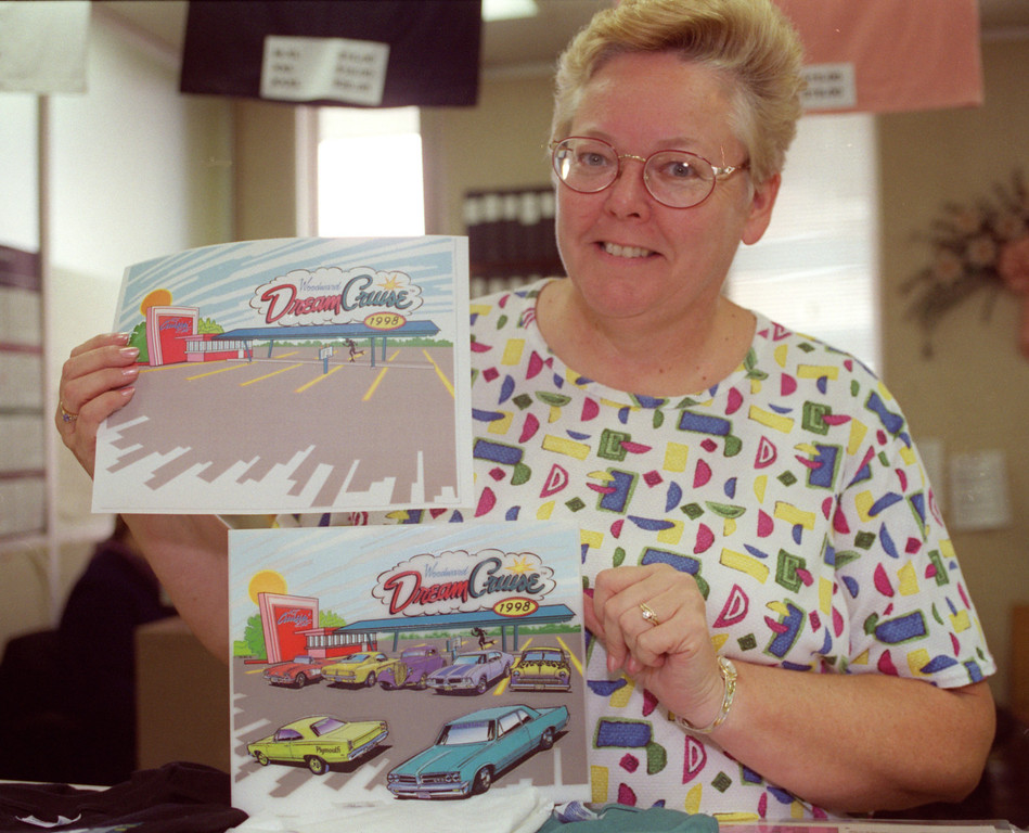 . Marsha Mellert , Recreation Supervisor at Ferndale City Hall, shows off the Before/After 7-City Commerative plaque with its colorform-like hotrods, that customers acquire in each city, in the city\'s Dept of Public Services and Recreation, where Dream Cruise merchandise can be bought.