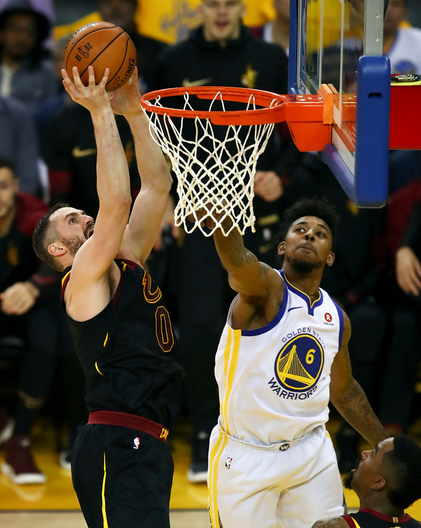 . Cleveland Cavaliers forward Kevin Love, left, shoots against Golden State Warriors guard Nick Young during the first half of Game 1 of basketball\'s NBA Finals in Oakland, Calif., Thursday, May 31, 2018. (AP Photo/Ben Margot)