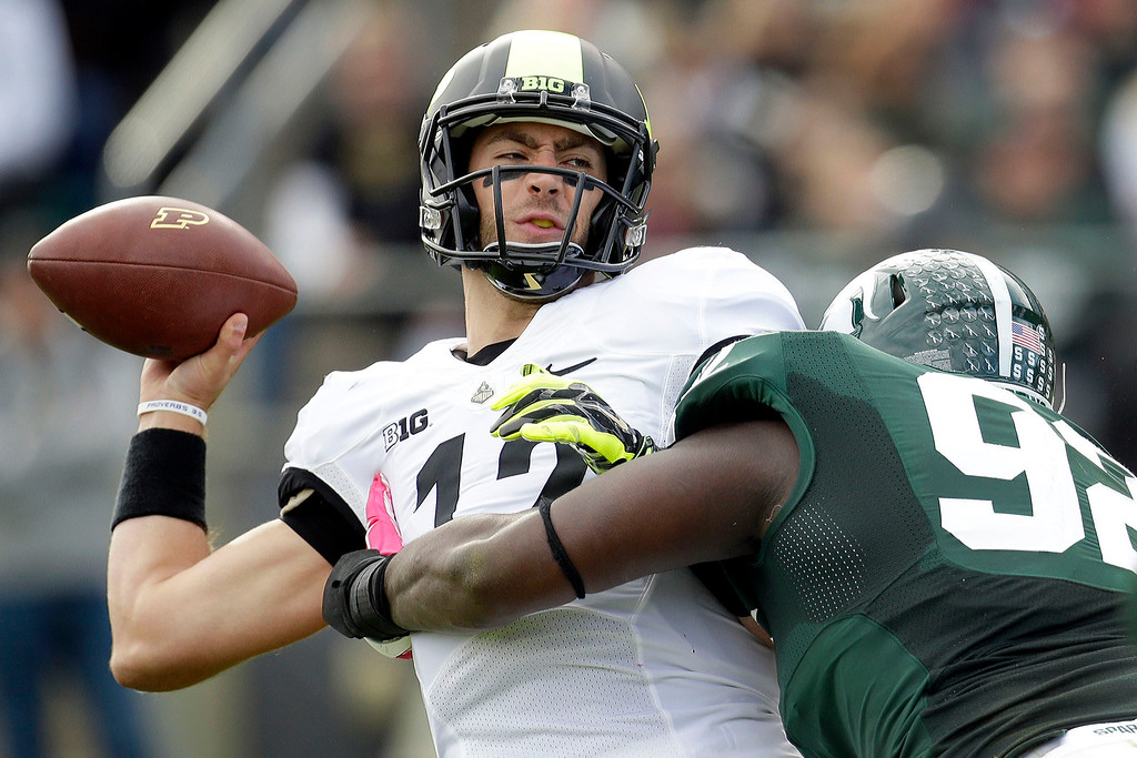 . Purdue quarterback Austin Appleby (12) gets hit by Michigan State defensive lineman Joel Heath (92) during the first half of an NCAA college football game in West Lafayette, Ind., Saturday, Oct. 11, 2014. Appleby completed the pass after being hit. (AP Photo/AJ Mast)