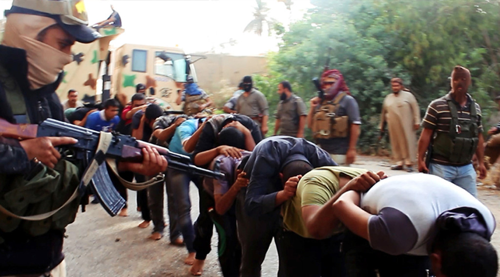. This image posted on a militant website on Saturday, June 14, 2014, which has been verified and is consistent with other AP reporting, appears to show militants from the al-Qaida-inspired Islamic State of Iraq and the Levant (ISIL) leading away captured Iraqi soldiers dressed in plain clothes after taking over a base in Tikrit, Iraq. The Islamic militant group that seized much of northern Iraq has posted photos that appear to show its fighters shooting dead dozens of captured Iraqi soldiers in a province north of the capital Baghdad. Iraq\'s top military spokesman Lt. Gen. Qassim al-Moussawi confirmed the photosí authenticity on Sunday and said he was aware of cases of mass murder of Iraqi soldiers. (AP Photo via militant website)