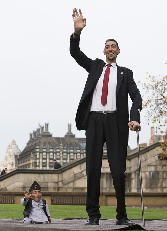 . Chandra Bahadur Dangi, from Nepal, (L) the shortest adult to have ever been verified by Guinness World Records, poses for pictures with the world\'s tallest man Sultan Kosen from Turkey, during a photocall in London on November 13, 2014, to mark Guinness World Records Day. Chandra Dangi, measures a tiny 21.5in (0.54m)  the same height as six stacked cans of beans. Sultan Kosen measures 8 ft 3in (2.51m).  AFP PHOTO / ANDREW  COWIE/AFP/Getty Images