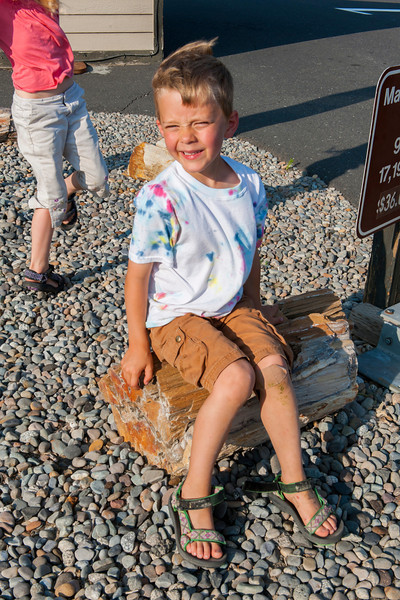 Aaron sitting on a chunk of petrified wood at the entrance to Wanapum State Park