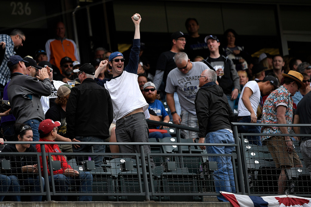 . Denver, CO - ARRIL 08: A Colorado Rockies fan takes home a foul ball at the home opener against the San Diego Padres at Coors Field. April 08, 2016 in Denver, CO. (Photo By Joe Amon/The Denver Post)