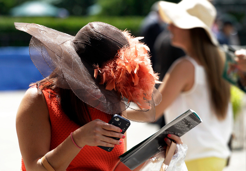 . Women wear hats as they arrive at Belmont Park before the Belmont Stakes horse race Saturday, June 8, 2013, in Elmont, N.Y. (AP Photo/Mark Lennihan)