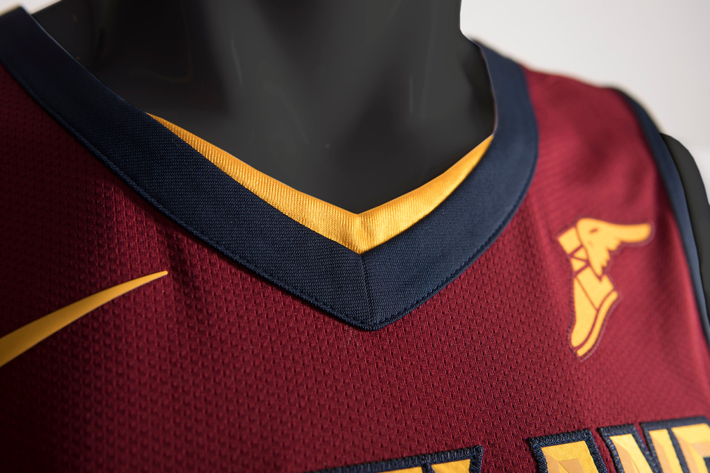 ". The Cavs new on-court look reflects the image of a shield to represent the team�s commitment to ""Defend The Land\"" and the spirit of resilience that is Cleveland. The shield, which was recently added to the Cavaliers updated logo collection and brand identity, is represented as a silhouette into the design of the uniform. A gold accent trim outlines the V of the collar, runs down the side and back shoulders of the jersey and onto the shorts to shape the edges of the armor.  Nike\'s famous Swoosh logo (right chest) and Goodyear�s iconic Wingfoot logo (left chest) will both appear on the Cavs player jerseys. (Courtesy Cleveland Cavaliers)"