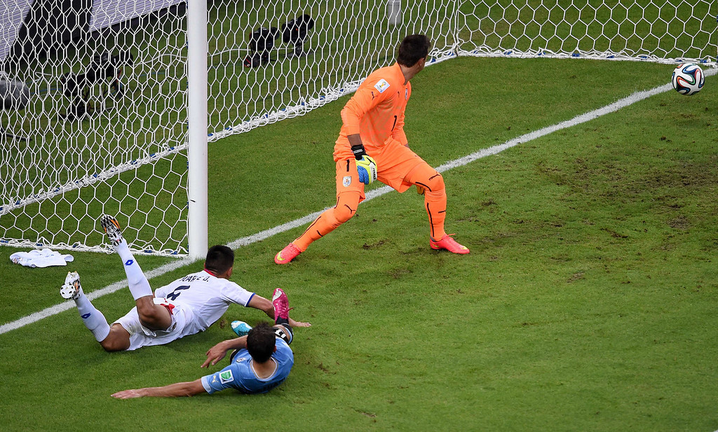 . Costa Rica\'s defender Oscar Duarte (L) heads the ball past Uruguay\'s goalkeeper Fernando Muslera (C) to score his team\'s second goal during a Group D football match between Uruguay and Costa Rica at the Castelao Stadium in Fortaleza during the 2014 FIFA World Cup on June 14, 2014.      AFP PHOTO / CHRISTOPHE SIMON